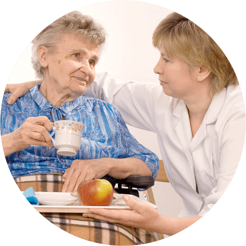 A caregiver assists her patient in eating