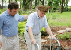 A caregiver assists his patient in taking a walk