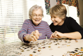 Caregiver and Elderly Playing Jigsaw Puzzle